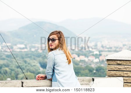 Young woman looking straight at you standing on the viewing platform on the background of the mountain town
