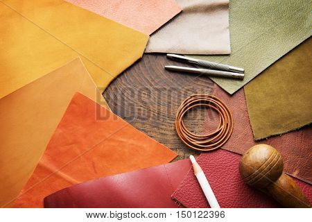Leather craft. Colorful pieces of beautifully colored or tanned leather and leather working tools on leather craftman's work desk .