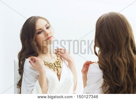 Young and beautiful girl trying jewelry. Bride doing make-up near the mirror.