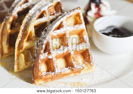 waffle with icing sugar whipped cream and blueberry dip