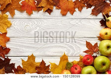 Autumn leaves and apples over old wooden background with copy space