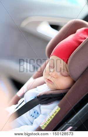 Six months old baby sleeping in car seat