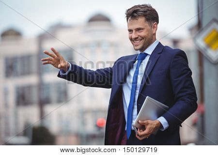 Handsome businessman calling for taxi on road