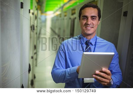 Portrait of technician using digital tablet in hallway of server room