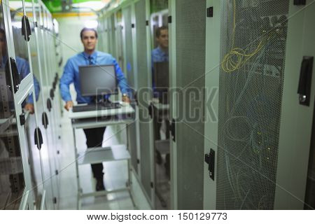 Technician walking with personal computer in hallway of server room