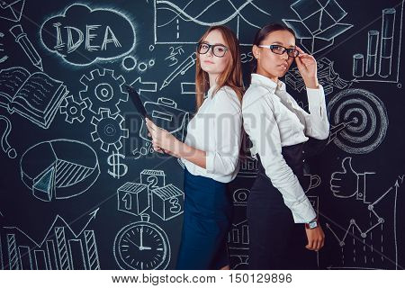 Europeans and Asian business women with glasses standing on a dark background with a pattern