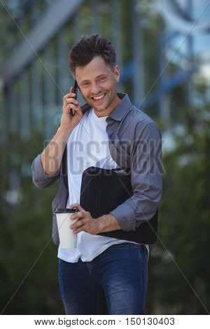 Handsome business executive talking on mobile phone outside office