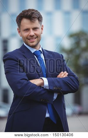Portrait of handsome businessman standing with arms crossed outside office