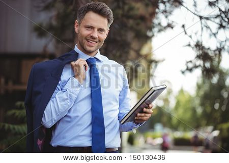 Portrait of handsome businessman holding dairy and blazer