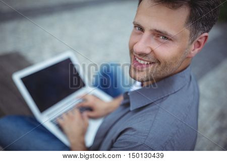 Portrait of handsome business executive using laptop outside office