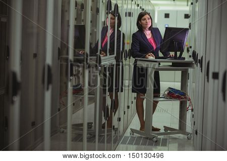 Technician personal computer while analyzing server in server room