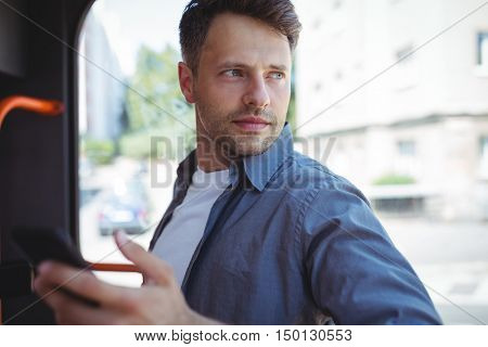 Handsome man looking through window while travelling in bus