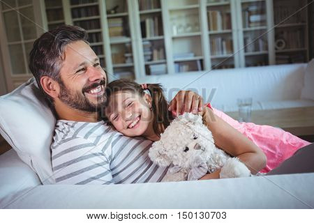 Happy father lying on sofa with daughter in living room