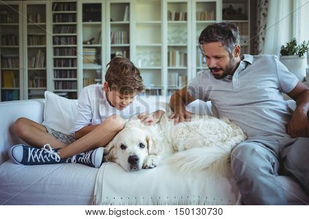 Father and son sitting on sofa with pet dog in living room at home