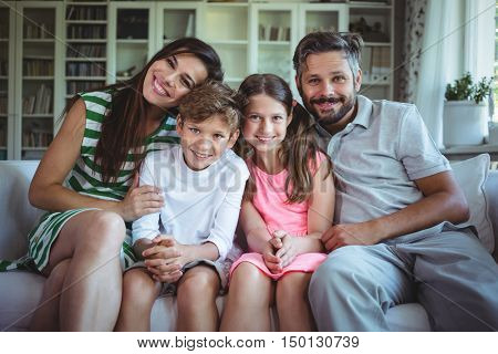 Happy family sitting on sofa at home
