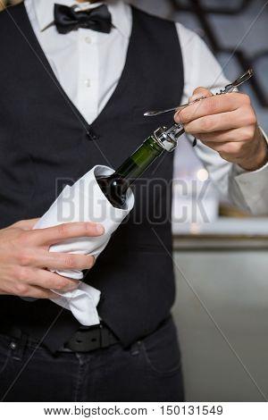 Bartender using corkscrew to open wine bottle in bar
