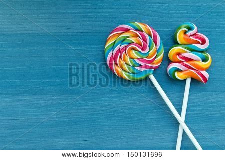 Two lollipops with many colors in a spiral on a wooden background