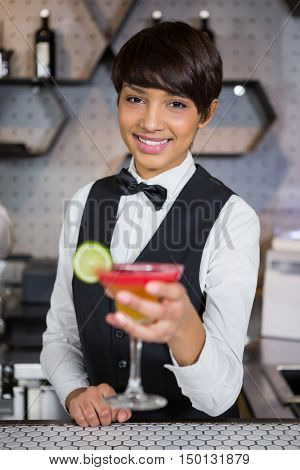 Portrait of smiling bartender holding glass of cocktail in bar counter at bar