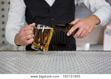 Mid section of bartender pouring beer on glass in bar counter