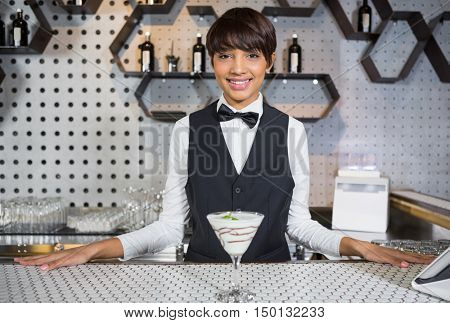 Portrait of smiling waitress standing in bar counter with glass of cocktail at bar
