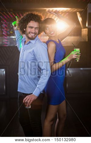 Cute couple dancing together on dance floor while having drink in bar