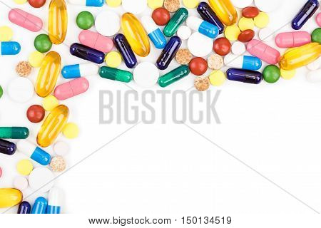 Various color pills and capsules on white background