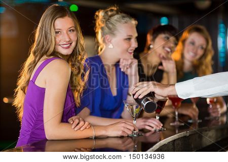 Waiter pouring cocktail in womans glass at bar counter in bar poster