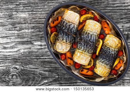 rolls-up of fillet of mackerel with grilled carrots cherry tomatoes lemon and spices in oval baking dish on dark wooden planks view from above
