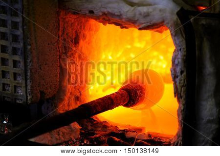 Manufacturing glass in a traditional oven the glassblower working on a handmade christmas bauble of melted glass on a rod poster
