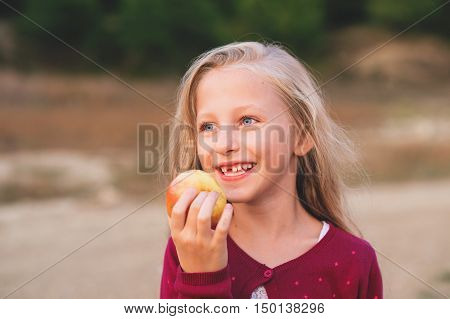 Losing baby teeth. Preteen child loosing teeth. Cut girl smailing.Closeup portrait of happy child eating yelow apple outdoors in autumn. poster