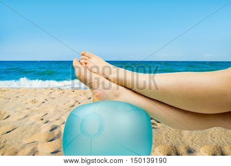 relaxed person with feet above the ball on the beach