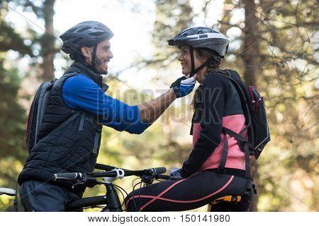 Man adjusting bicycle helmet of a woman in countryside