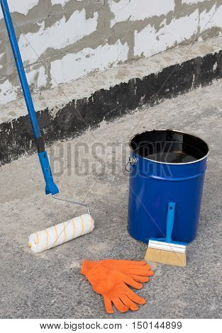 Ceiling brushes Brushes and a bucket of bitumen primer for waterproofing against the background of a brick wall. Tools waterproofing