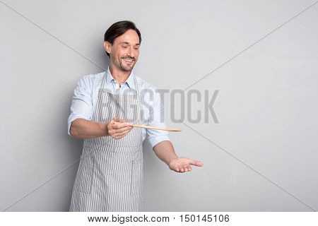 Taste it. Happy Handsome man holding a wooden spoon while pretending like cooking something