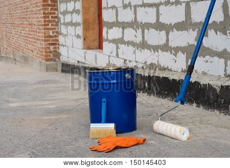 Tools for waterproofing. Mittens roller ceiling brushes and a bucket of bitumen primer