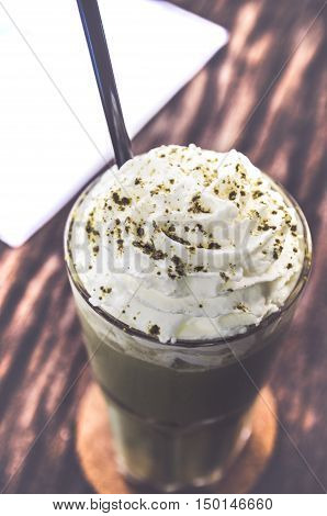 green tea frappe drink on wood table