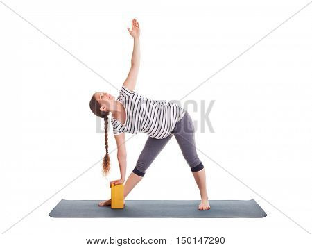 Pregnancy yoga exercise - pregnant woman doing asana Utthita trikonasana - extended triangle pose with block isolated on white background