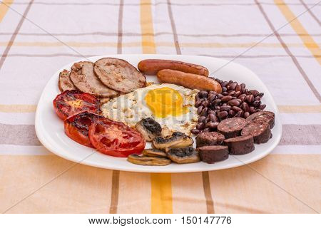 Full English fried breakfast with bacon, egg, sausages, black pudding, mushrooms. Grilled tomatoes and baked beans.
