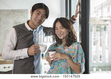 couples of asian young man and woman with coffee cup in hand standing relaxing in home living room
