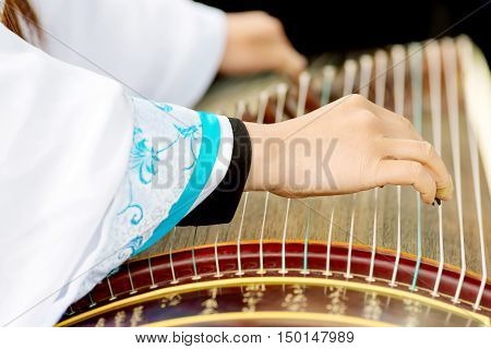 A girl is playing Guzheng.The guzheng or gu zheng also simply called zheng is a Chinese plucked zither. It has 18 or more strings and movable bridges.