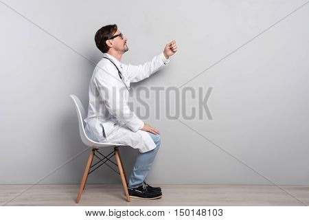 I will cure you. Young handsome talented doctor in smock gesturing like diagnosing his patient