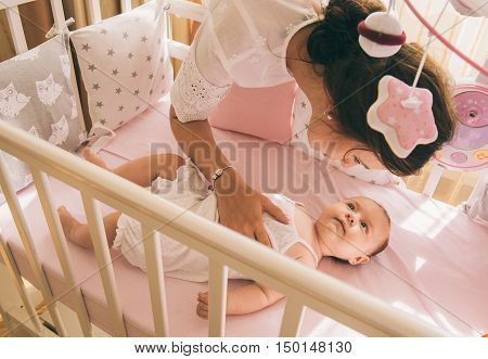Close-up portrait of a happy mother laughing with cute baby in crib