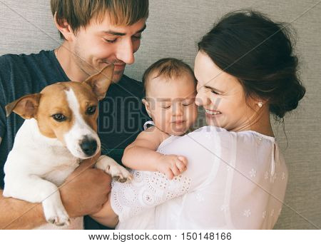 Family close-up portrait - parents their little cute baby girl and their pet - jack russel terrier dog