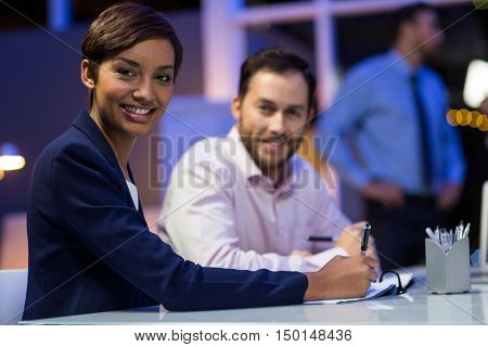 Smiling businesspeople preparing document in conference room at office