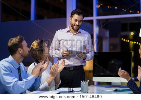 Businesspeople applauding on their colleagues presentation in conference room