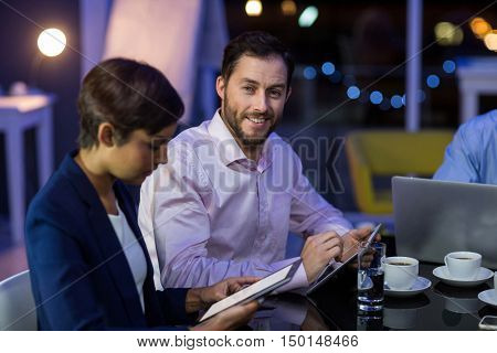 Businessman and businesswoman using digital tablet in office at night