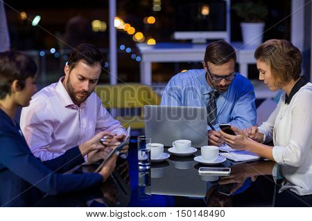 Businesspeople working in office at night