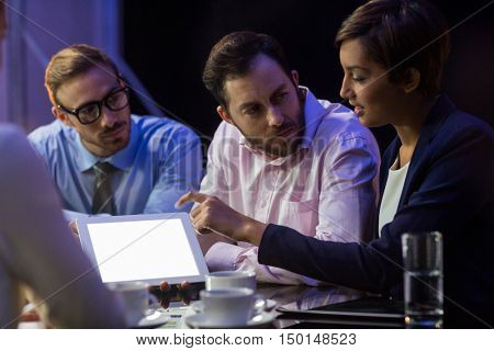 Businesswoman discussing on digital tablet with her colleagues in office