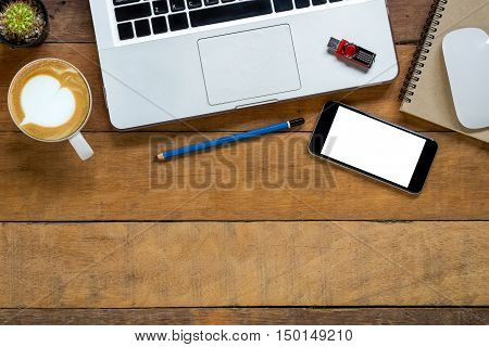Office stuff with blank screen smartphone pencil leather notebook flatdrive laptop mouse and cup of coffee. Top view with copy space.Office desk table concept.