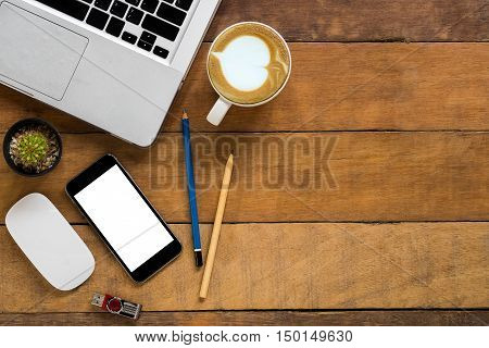 Office desk table with blank screen smartphone mouse flashdrive pencils laptop and cup of coffee. Top view with copy space.Office desk table concept.